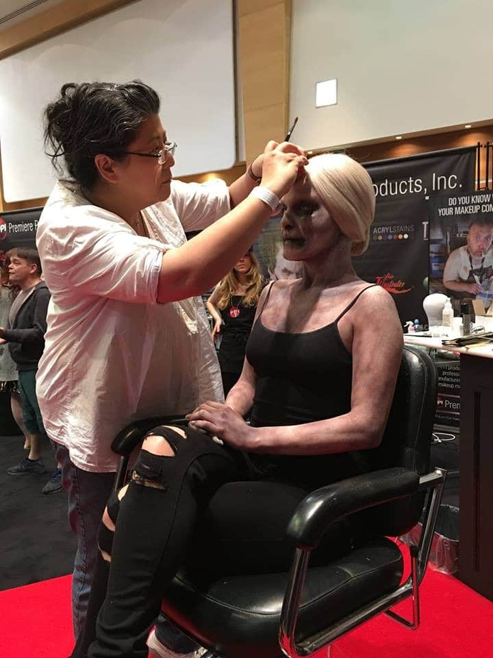 Karen adjusts a wig for their UMAe demo.  Image by Warpaint Magazine